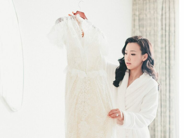 Bride in robe looking at wedding dress