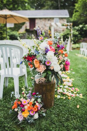Colorful Flower Arrangement on Rustic Tree Stump and White Backyard Chairs