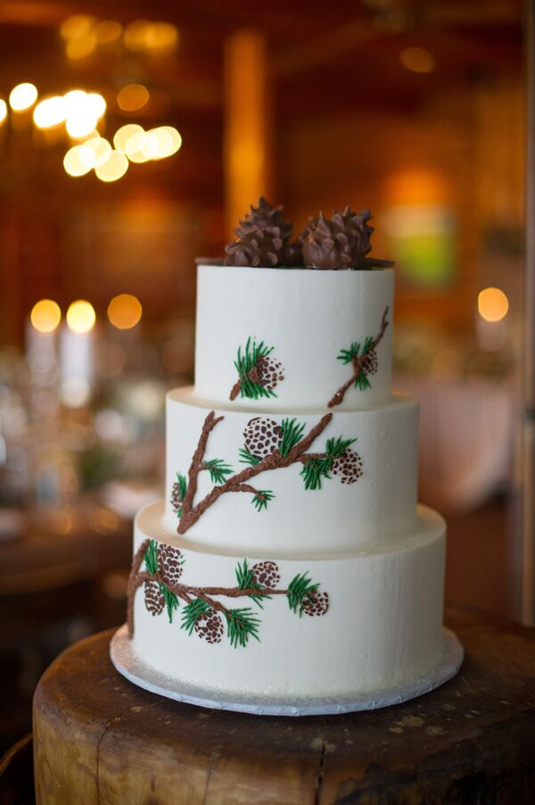 "Anne and Andrew enjoyed a three-tier white buttercream wedding cake decorated with pine and pinecone paintings. ""We ordered our cake from Rachel at Intricate Icings, and worked with her to create a cake that matched our rustic elegant decor,"" Anne says. ""It was as gorgeous as it was delicious, and all of it free of fondant. Rachel is a true artist."""