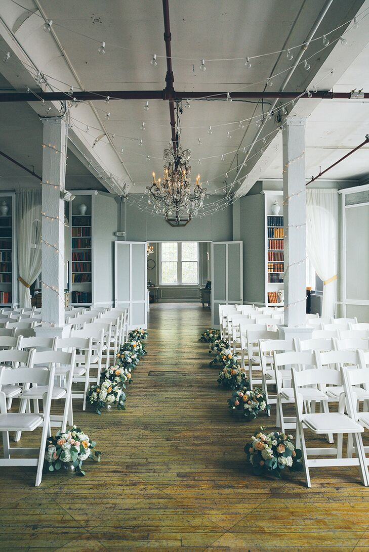 Modern Loft Venue With Flower Aisle Decorations And White Folding Chairs