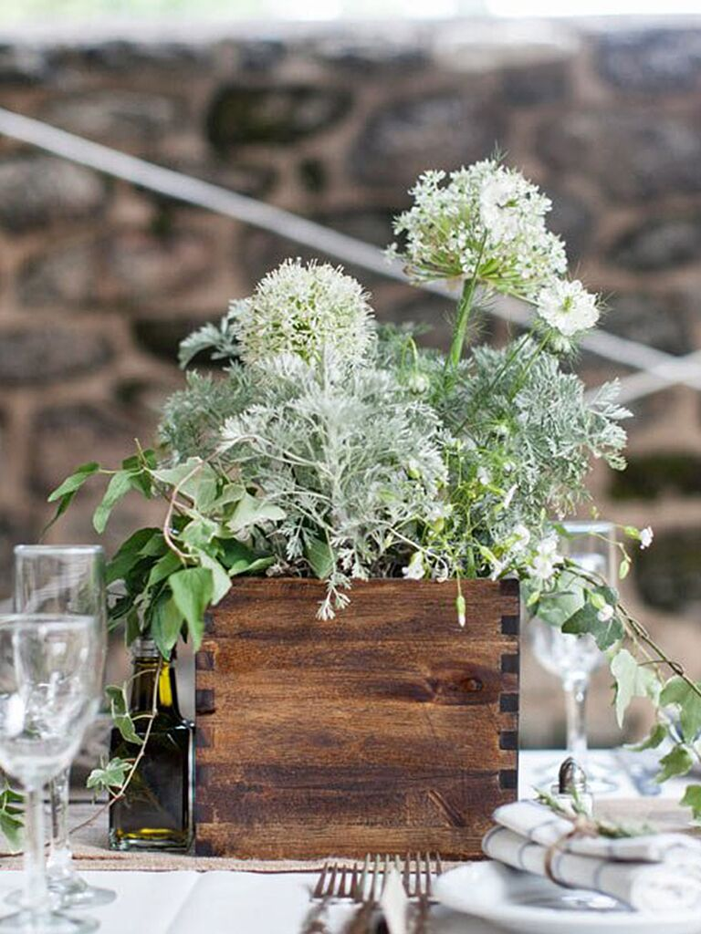 Natural romantic table centerpiece with flowers and greenery for a wedding reception