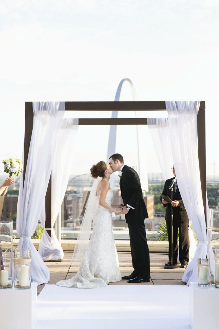 Becca and Phil chose to hold their wedding at the Four Seasons because of the stunning view of downtown St. Louis from the rooftop terrace where they held their ceremony. The couple exchanged vows under a modern wooden arbor draped with airy white fabric.