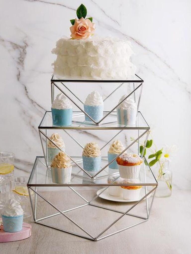 Set of three metal geometric tiered wedding cake stand with single-tier cake on top