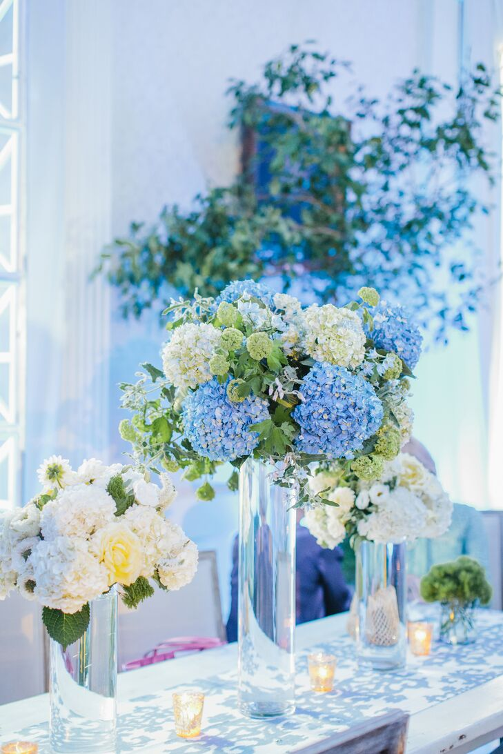 "A mixture of blue and green hydrangeas filled tall glass centerpieces. ""I wanted the florals to match the blue and white ikat pattern and marina blue linens and draping,"" says Colleen."