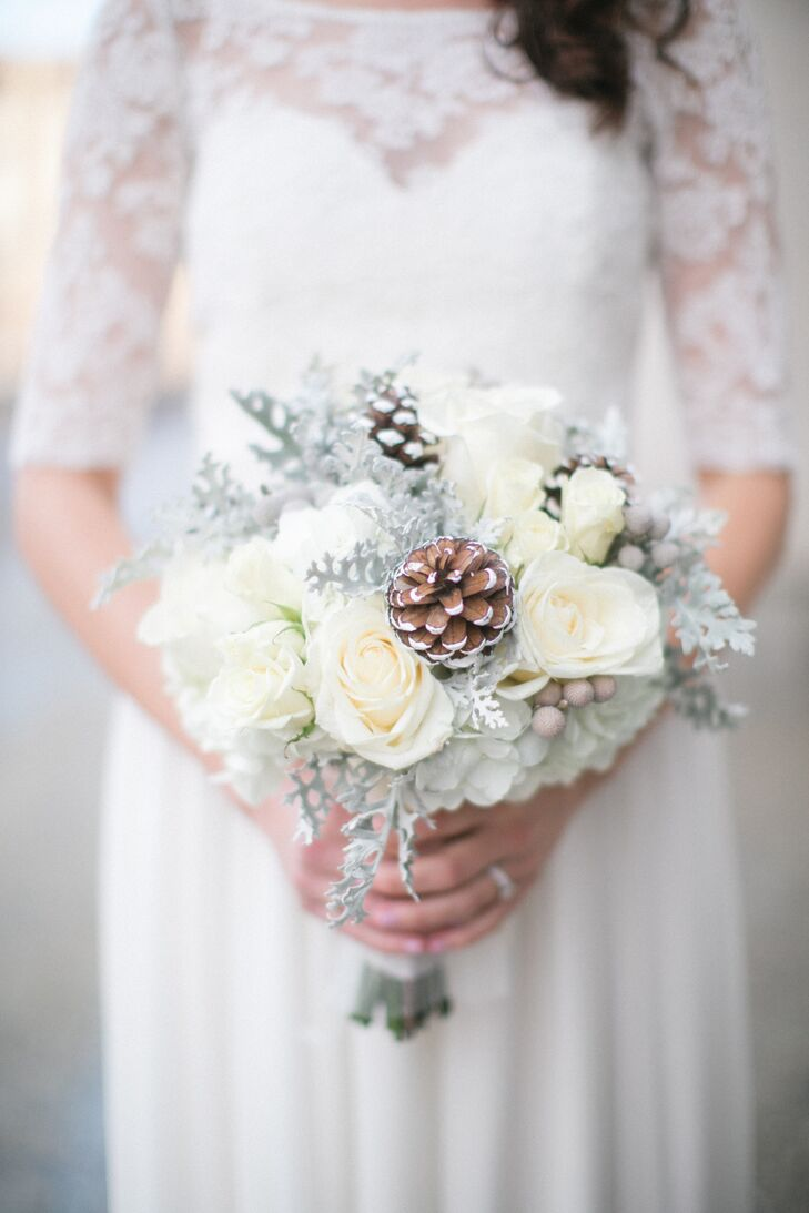 Drawing inspiration from the season, as well as Amy and Matthew's romantic, pinecone theme, Studio B Floral got to work creating wintry arrangements for the centerpieces, boutonnieres and bouquets. Ivory roses and hydrangeas served as the base for Amy's bouquet, with silver brunia berries, pinecones, and dusty miller adding a touch of winter woodland flair.