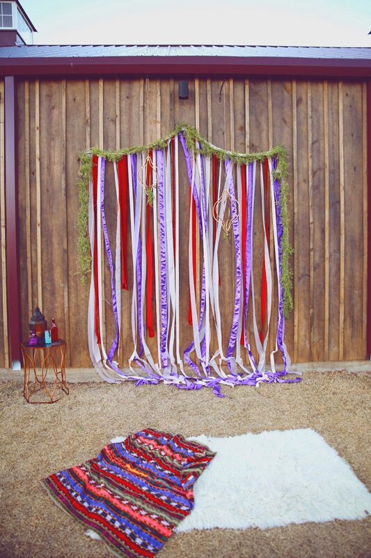 While the couple's vision truly came to life at the reception, Pretty Lovely Events ensured the ceremony was packed with panache and personality as well. A colorful ribbon backdrop decorated with gold dream catchers and a lush green garland provided a striking focal point for the ceremony, while details like textured throw rugs brought an element of coziness to the outdoor space.
