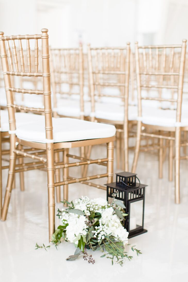 Gold chiavari chairs and a gold sequined aisle runner added color to the all-white hangar where Kelsey and Andrew hosted their ceremony. Lanterns and bouquets of white hydrangeas and baby's breath enhanced the romantic vibe.