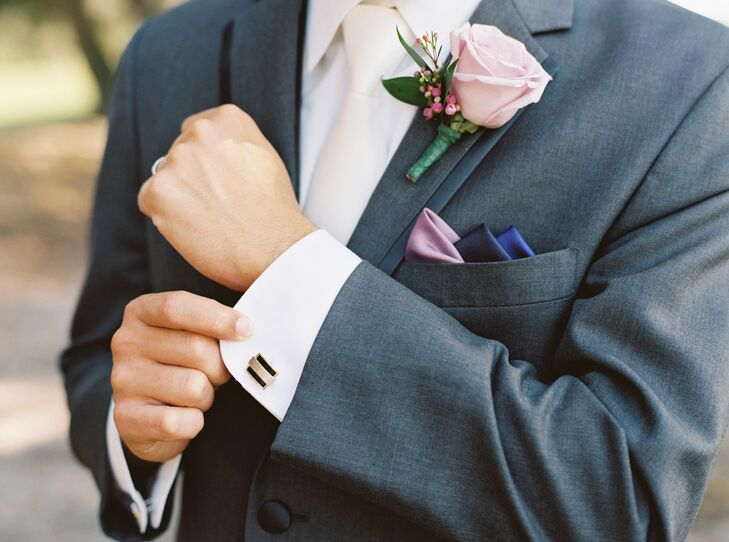 Josh incorporated the couple's purple wedding color and mauve accent hue in his wedding-day look. He paired his gray suit from Men's Wearhouse with a mauve rose and pink hypericum berry boutonniere. He also donned a triple pocket square in purple, indigo and mauve.
