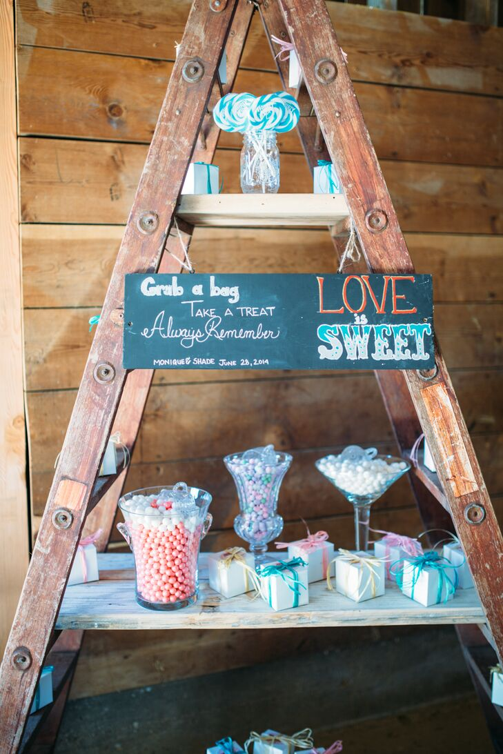 """During the reception, guests wandered into the barn to pick out sweets and treats from the """"candy store"""" display. They picked from a range of candy and cupcakes boxed in colorful packaging, with a chalkboard sign that read """"Love Is Sweet."""""""
