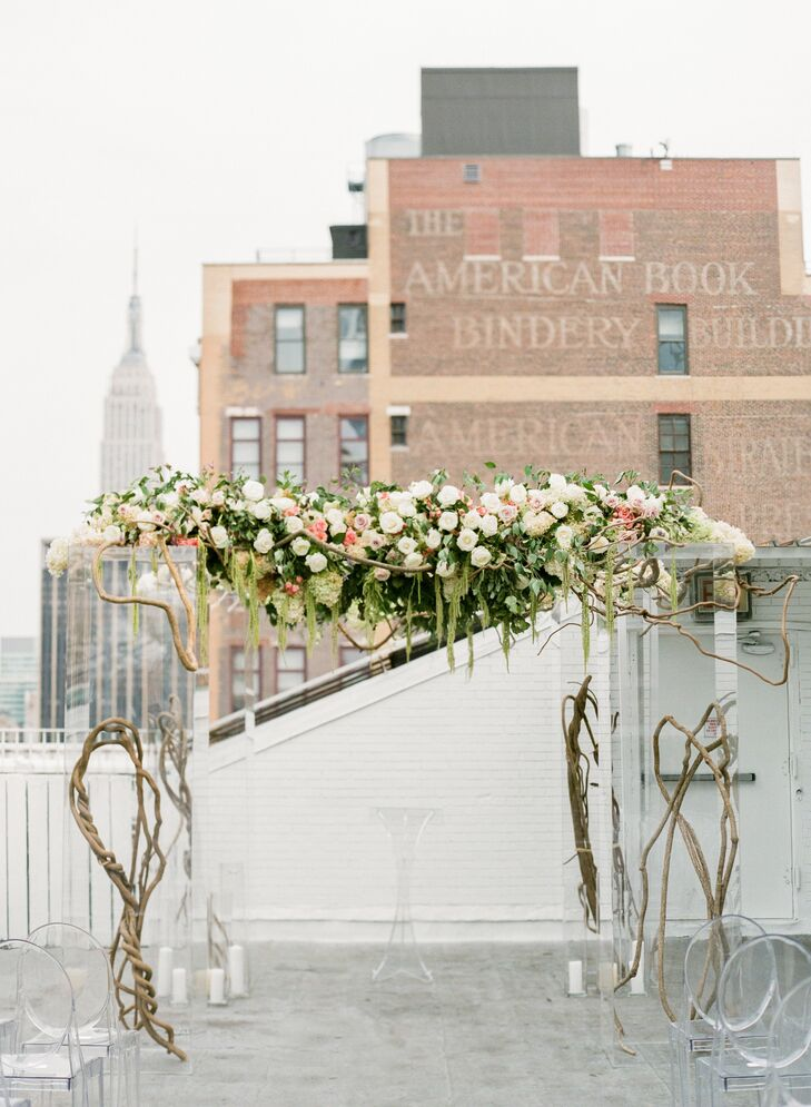 Mia and Jake's chuppah perfectly reflected the couple's modern, romantic vision with its fusion of natural and contemporary elements. Curly willow branches and Plexiglas columns served as the base for the striking structure, while a cascading garland of green amaranth, greenery, vines and blush and ivory blooms brought a secret-garden feel to the decor.