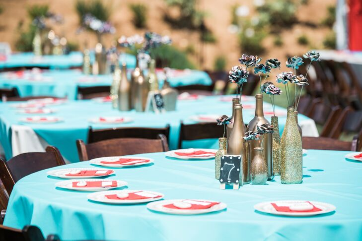 "Jess and Dave chose turquoise and red as their wedding colors, a perfect complement to their ""geek chic"" theme. The centerpieces consisted of spray-painted gold and glitter bottles holding two to four paper flowers."