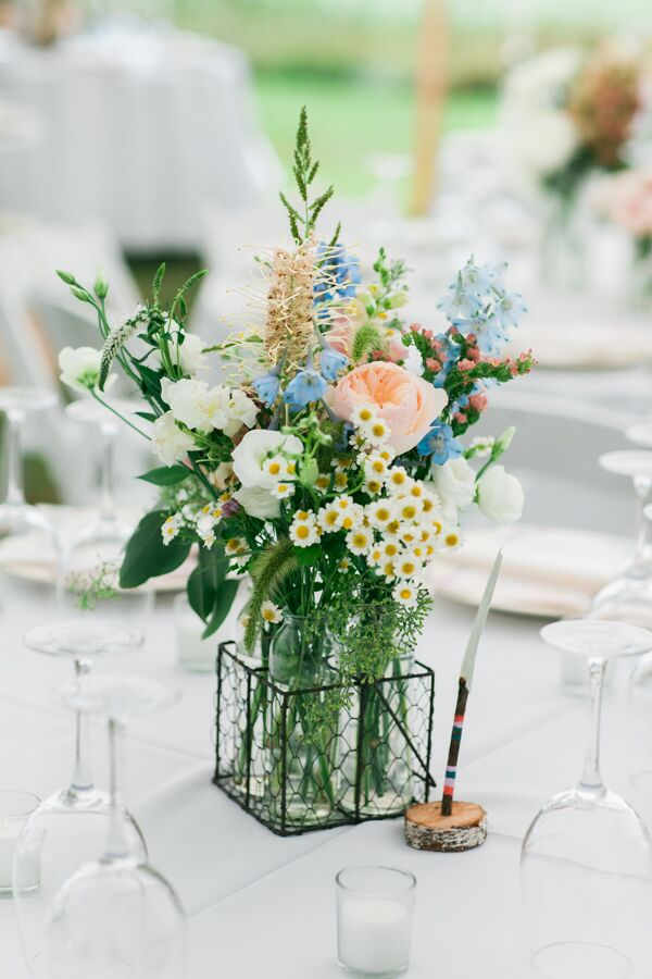 Jordan's mother, the genius behind Seagrass Florals, channeled the wild feel of the gardens at Megan's parents' home in North Yarmouth, Maine. Each arrangement was filled with a mix of colorful wildflowers and classic pastel blooms.