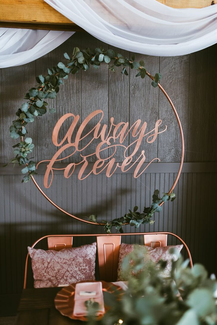 "Personal touches continued into the reception décor. ""At the front of our table, we had a hoop covered with greenery and our favorite saying 'Always & Forever' hanging behind us,"" Trisha says."