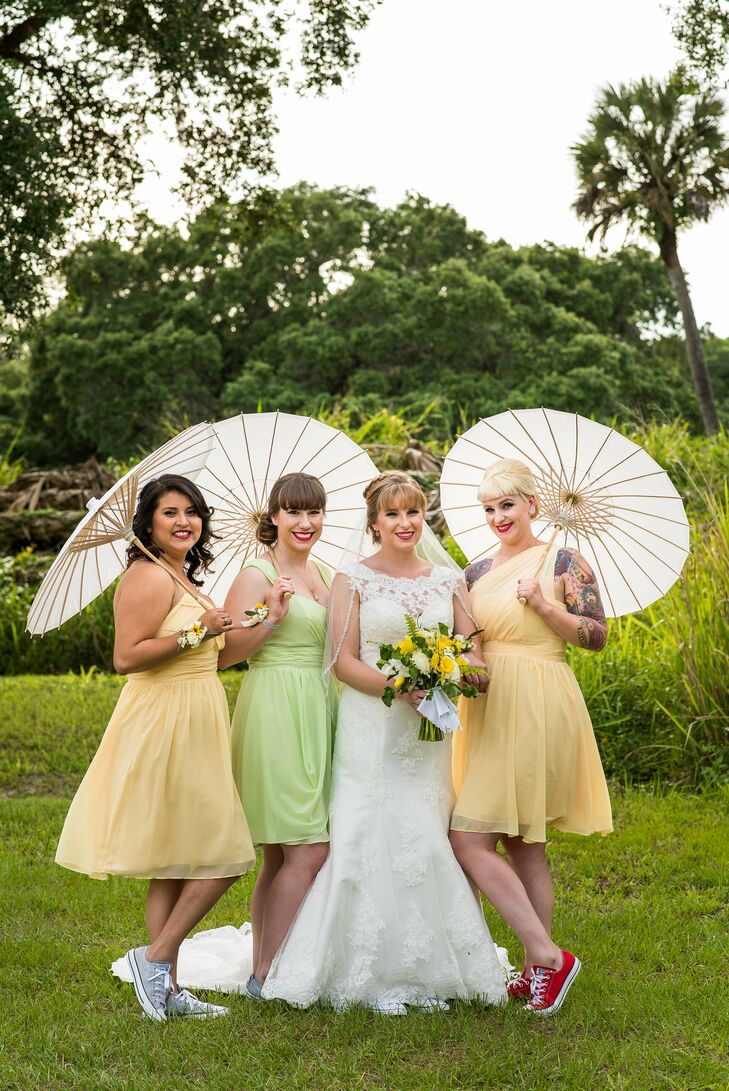 The bridesmaid looks fit the spring affair to a T with short yellow and light green chiffon dresses by Alfred Angelo. Each woman chose her own look and changed things up with a funky pair of colored Converse shoes. They also switched out bouquets for chic parasols and lush corsages.
