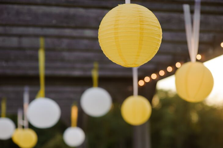 White and yellow paper lanterns hung above the couple during the ceremony.