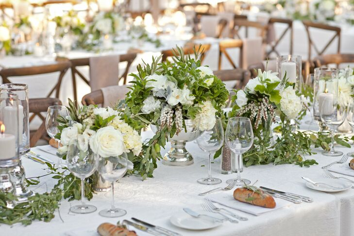 Ivory blossoms like lily of the valley, lisianthuses and garden roses were arranged with lush greenery in silver pedestal vases.