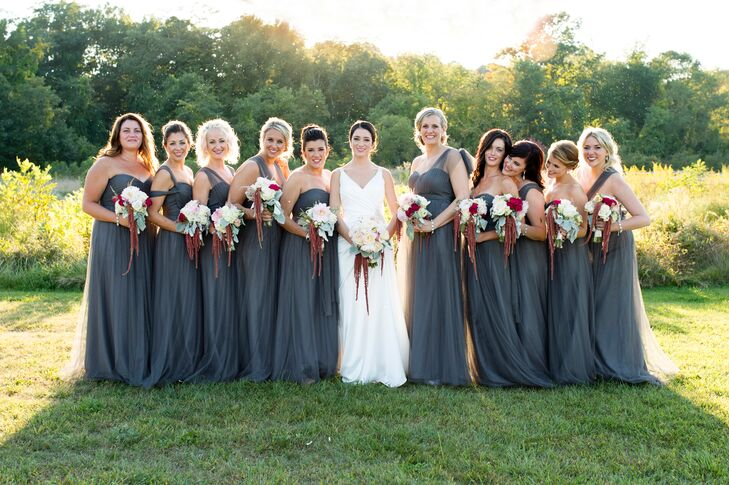 When looking for bridesmaid dresses, MacKenzie wanted to find a style that all the girls would love, and that would go with the wedding's sophisticated yet subtly bohemian theme. Jenny Yoo's Anabelle dress offered just that. After choosing a steel gray hue, MacKenzie had each bridesmaid choose a style that fit her personality and body type. To complete the look, she gave each a statement diamond bracelet and asked her to pair it with diamond stud earrings.