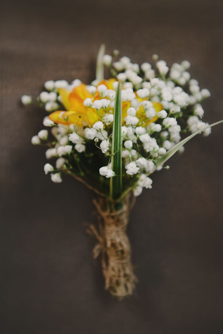 The boutonnieres were kept on the simple side, with small bunches of baby's breath tied with twine. For a hint of color, a few yellow flowers were added to the mix.