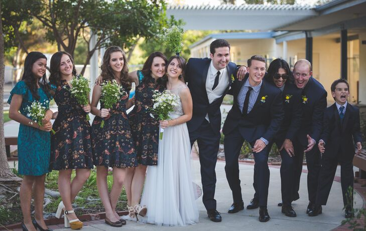 Beth and Jonathan stood in the middle of their wedding party wearing accents of navy blue, which went along with the blue and yellow palette. Groomsmen had a single yellow button mum pinned to their navy blue lapels and bridesmaids held bouquets filled with small daisies.