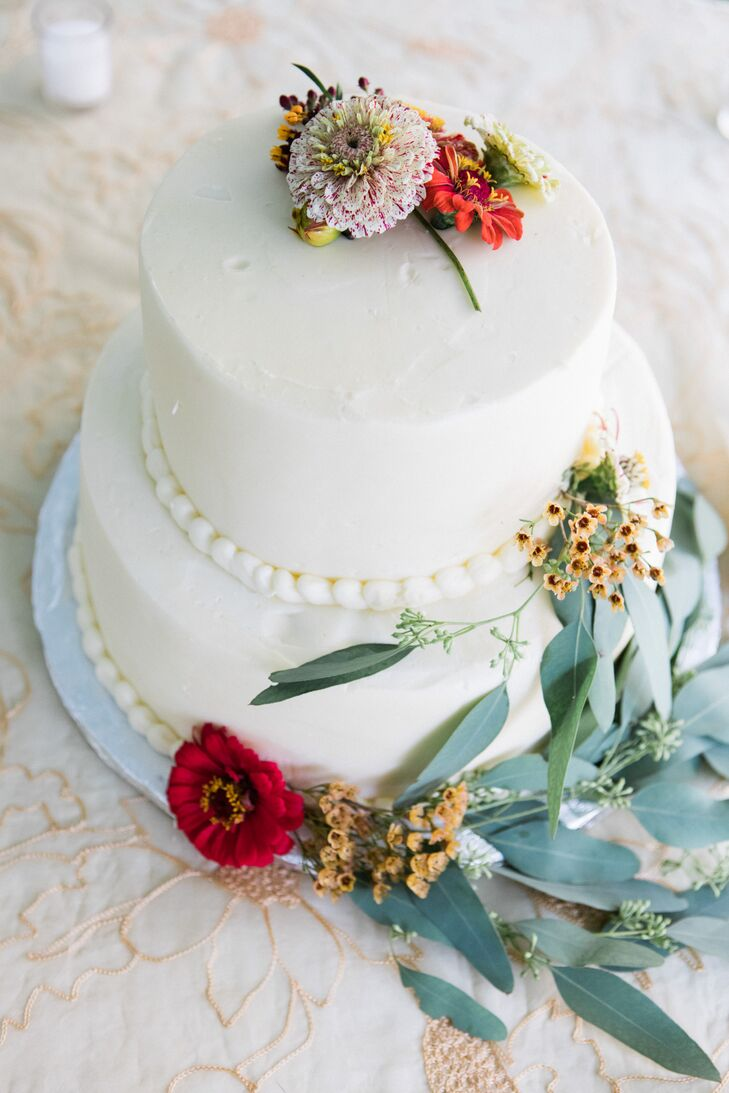 Gold and red flowers and a touch of greenery carried a simple autumn theme onto the white buttercream cake.