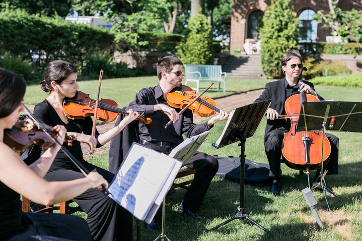 """To set the tone, the Vogue Music String Quartet performed as guests arrived and throughout the ceremony. Tim and the wedding party made their entrance to """"All of Me"""" by John Legend, while Canon D served as the sound track for the bridal processional."""