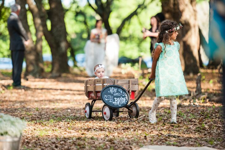 Sarah and Sean's flower girl's look was different from the rest of their wedding party's. She made her procession in a mint, rosette-detailed dress and bold star-accented tights. She also wore a sweet pink and white flower crown. Their littlest attendant was pulled in the wooden cart behind her.