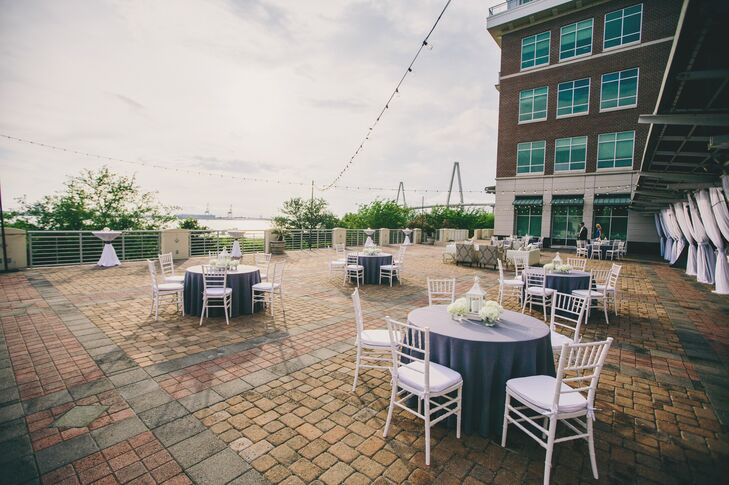 Since their reception venue, Harborside East, had gorgeous views of the Charleston Harbor, the couple took advantage of the outside space with a lounge area and tables for seating. The tables were decorated with white chiavari chairs, gray table linens and white lantern centerpieces.