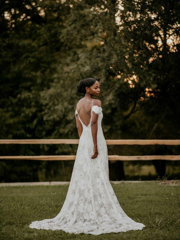 Bride wearing cold-shoulder wedding dress with plunging back at outdoor summer wedding ceremony