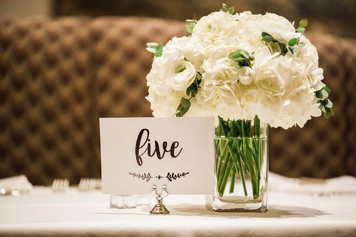 """Tables were topped with calligraphed numbers and simple glass vases filled with ranunculus. """"I did my own flowers to save on the budget and went to the LA Flower Market downtown the morning before,"""" Jon says. """"I chose white hydrangeas and white ranunculus with accents of baby eucalyptus."""""""