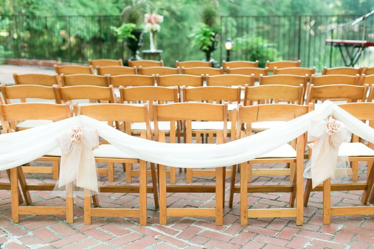 The ceremony took place on the front brick patio of the Southern home, allowing nature to be the main focus of event. Draping fabric was hung on the back row of chairs to keep it simple and subtle, while a single tall floral arrangement was placed at the front of the altar.