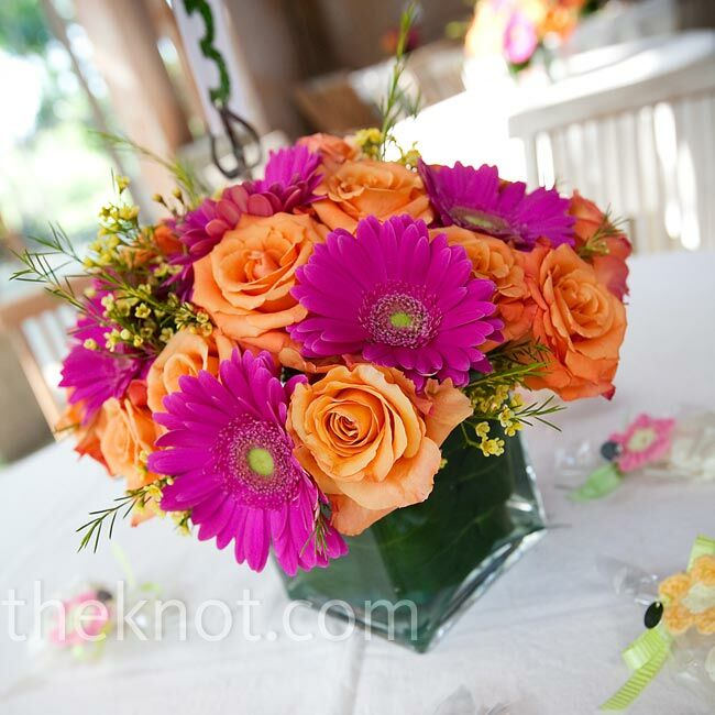 The centerpieces were vibrant combinations of hot pink gerbera daisies, orange roses, and yellow wax flowers in simple clear vases.