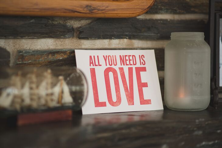 "A small white sign with the screen print ""All You Need is Love"" stood on the mantle at the reception venue."
