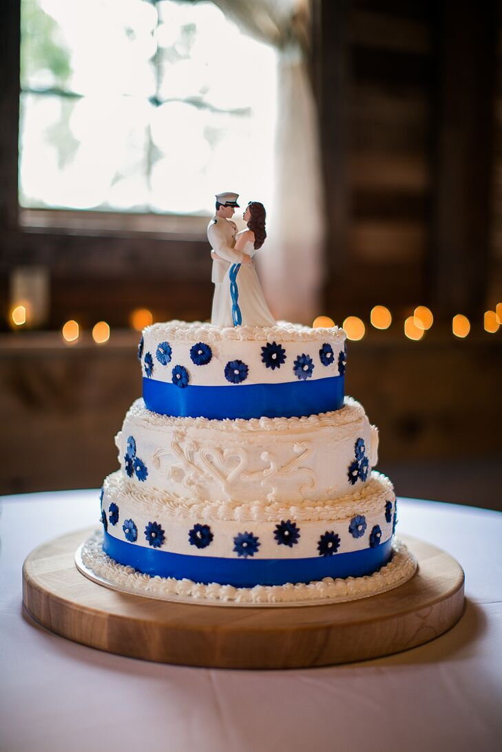 Josh's mother made the ivory wedding cake, which was decorated with blue sugar flowers and ribbon around the base of the layers. A bride and groom figurine set resembling Justine and Josh served as the cake topper.