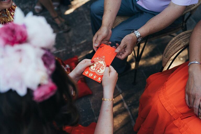 Red envelope being passed during Chinese wedding ceremony