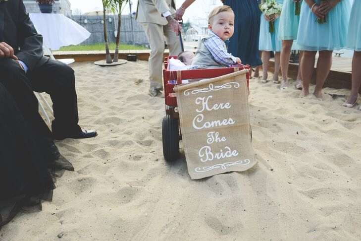 """Our nephews were pulled in on a Fire Island Flyer wagon down the aisle by the matron of honor—they totally stole the show!"" says Caitlin."
