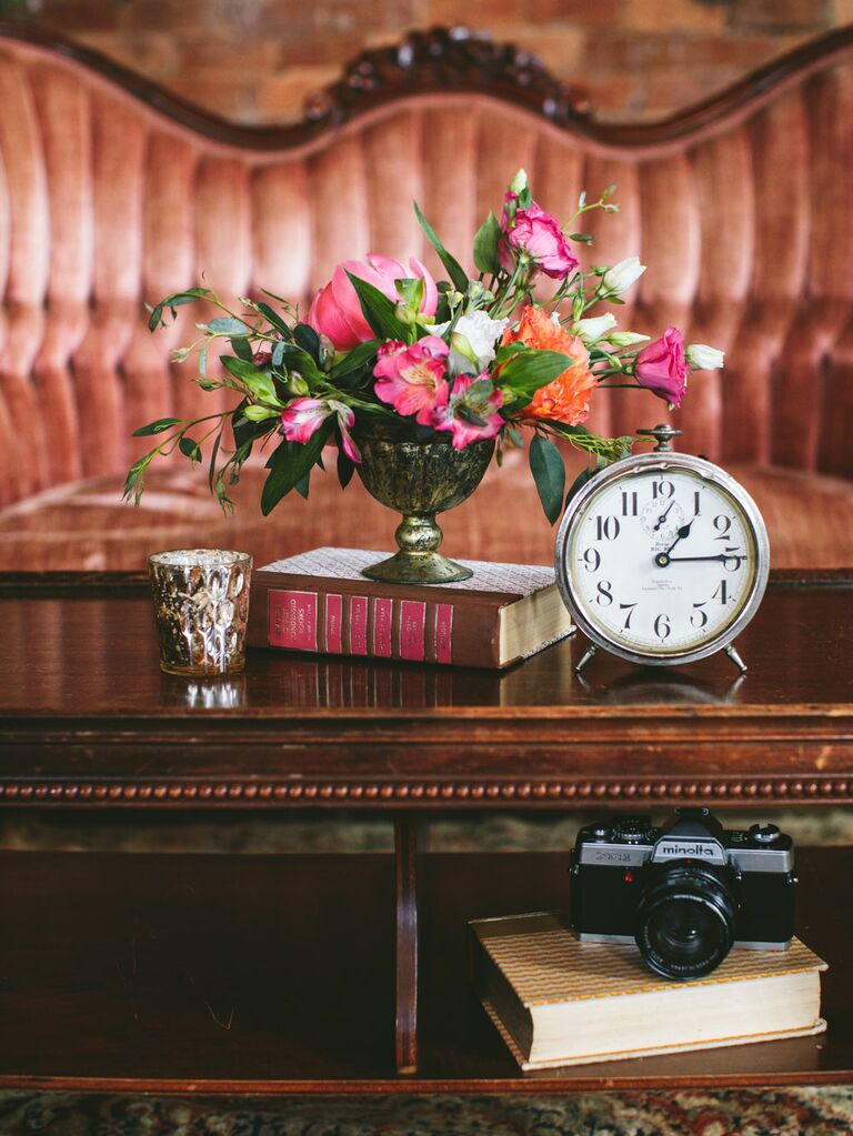 Vintage wedding decoration vignette with heirloom clock, candle, bouquet of flowers and antique book