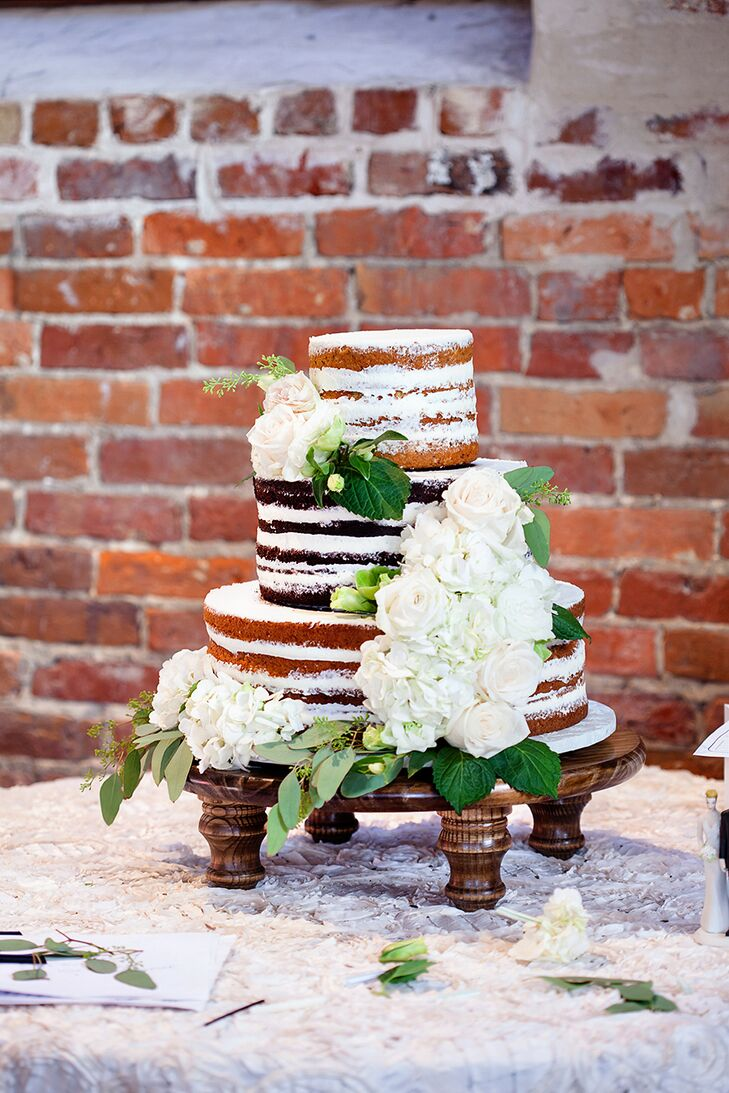 The pair featured a three-tier multilayered naked cake with tiers of ascending size. The cake was decorated with fresh flowers and greenery and photographed beautifully against the exposed brick.