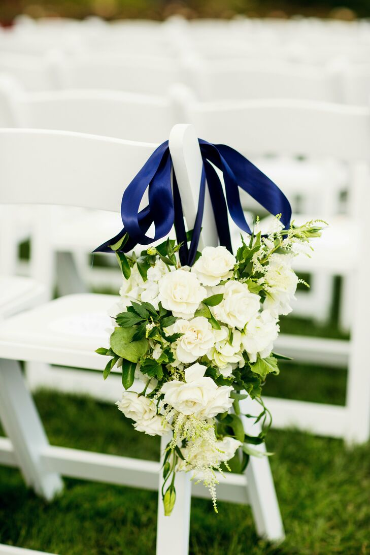 Bunches of white flowers tied with a navy blue ribbon hung on the aisle chairs.