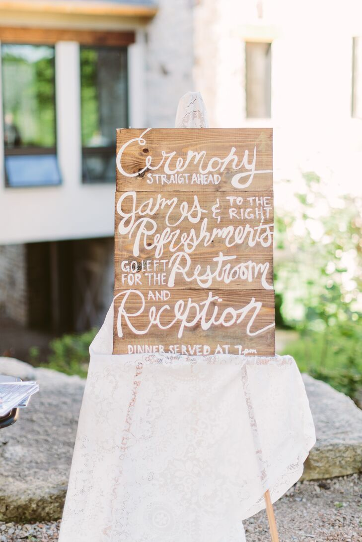 A wooden board displayed directions to different sections at Givens Farm, propped up on an easel covered with a white cloth accented in lace. This helped guests find their way throughout the day.