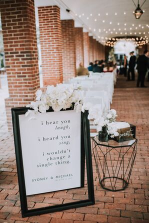 Formal Sign with Black Typography and White Flower Arrangement