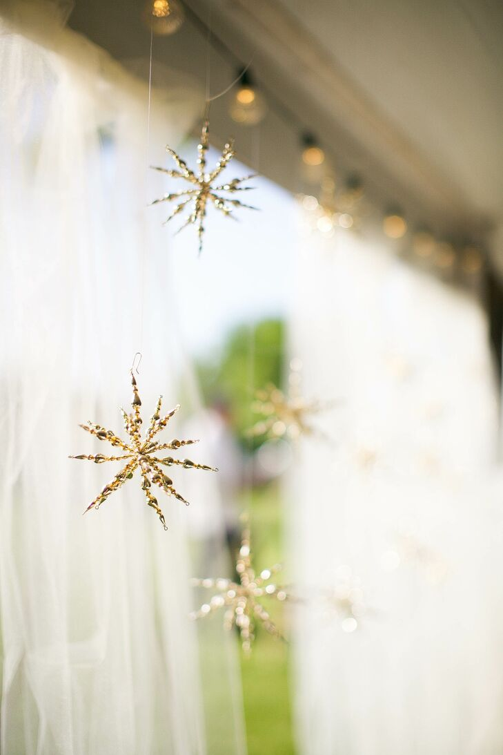 "Delicate gold hangings, like these glitter stars, and string lights were a simple way for the couple to deck out the outdoor reception area, which was on a friend's property in Delevan, Wisconsin. Here, the purple and gold theme continued with hand-painted purple vases and gold accents. ""We loved that we could decorate the inside of the tent with gorgeous lights, candles, and florals, but still have yard games, a s'mores bar, and a bonfire going outside,"" Anna says."
