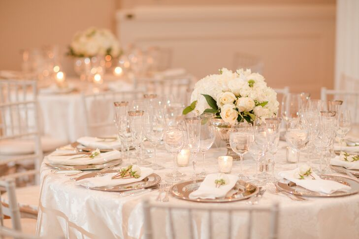 Centerpieces at this reception were simple, with white roses and hydrangeas arranged in mercury glass pedestal vases. The tables also had a few scattered votive candles.
