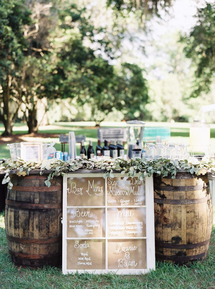 The barrel-lined bar perfectly fit their decor! Instead of wooden chairs, a rustic element was added with twin barrels. Eucalyptus garlands, which matched the head table's centerpieces, also cascaded down the front. To make things more personalized, Laurie's sisters made a shabby-chic window sign listing every beer, wine and nonalcoholic drink in stock.