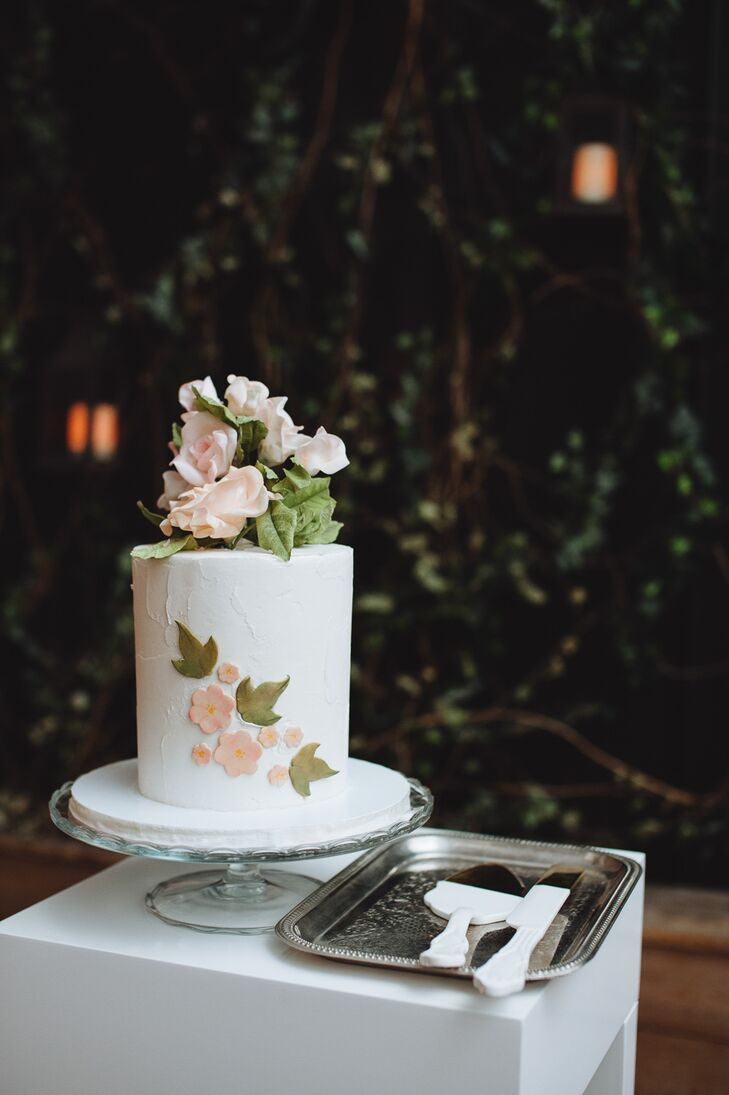 After a traditional sit-down dinner, Whitney and Ryan cut into their petite wedding cake. The one-tier confection featured stucco-style buttercream in a classic shade of white and pale pink fondant flowers. With Whitney's preference for blush roses in mind, the pros at Lael Cakes topped the cake with a fresh bundle of the blooms.