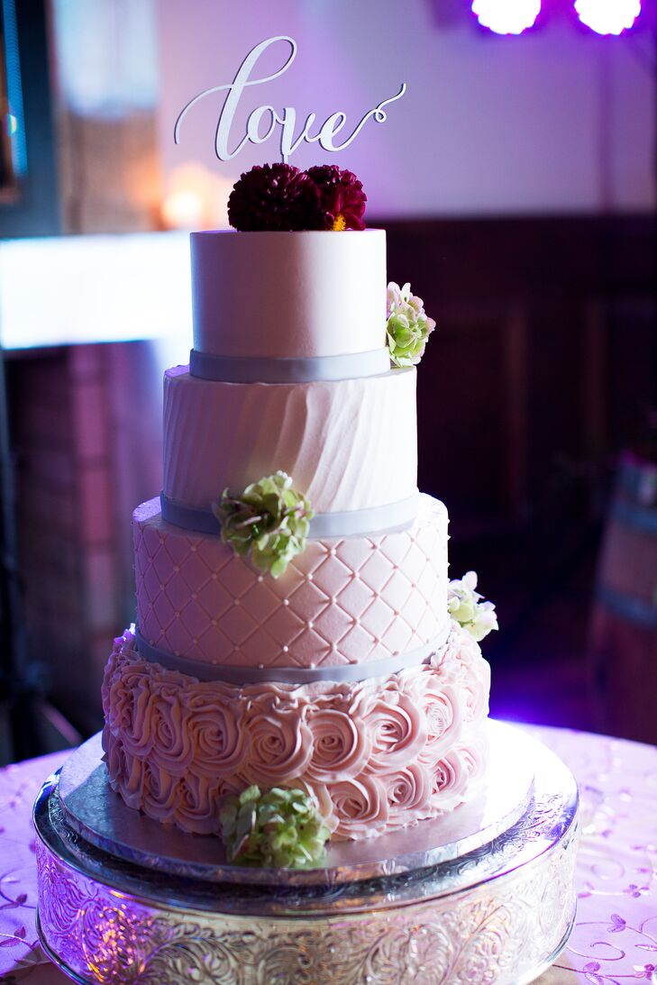 An ivory wedding cake with fresh floral accents was made by Cindy's Cakery. The cake had four tiers made of french vanilla with raspberry, chocolate with ganache, lemon with lemon curd and almond with strawberry.