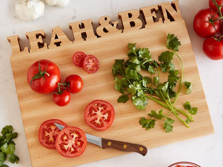 Wooden chopping board with couple's names carved into the top edge
