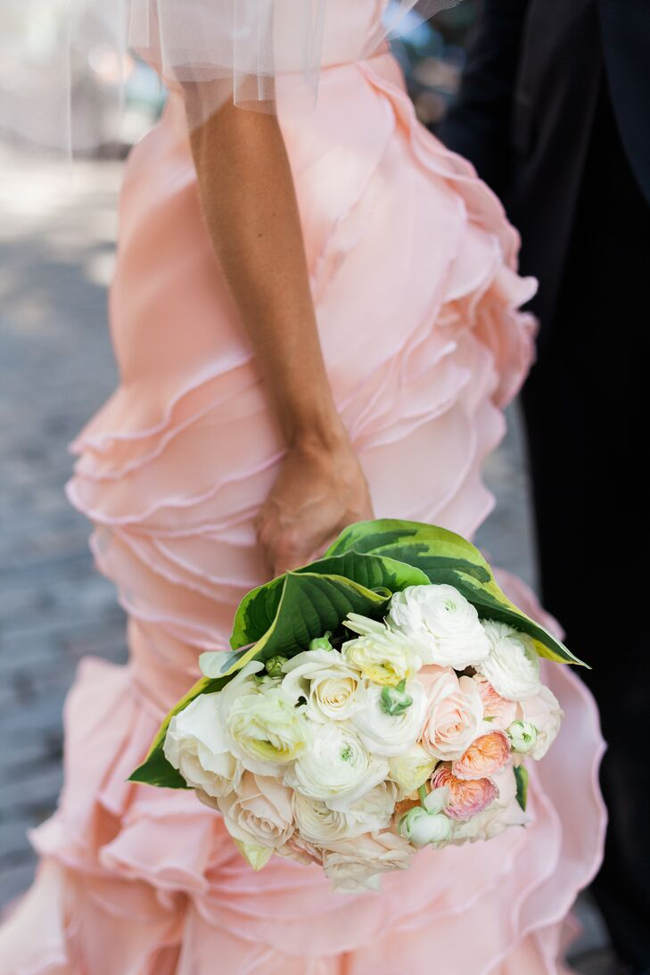 A lush bouquet of ranunculus and garden roses popped against the bride's pink Leanne Marshall dress.
