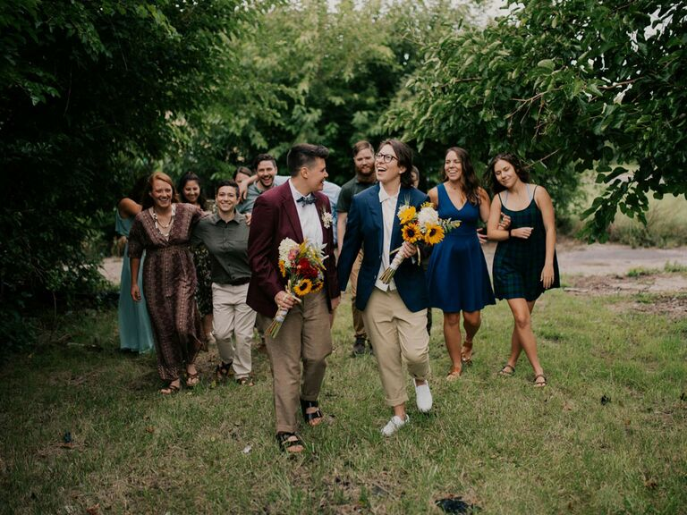 Couple holding sunflower bouquets with wedding party