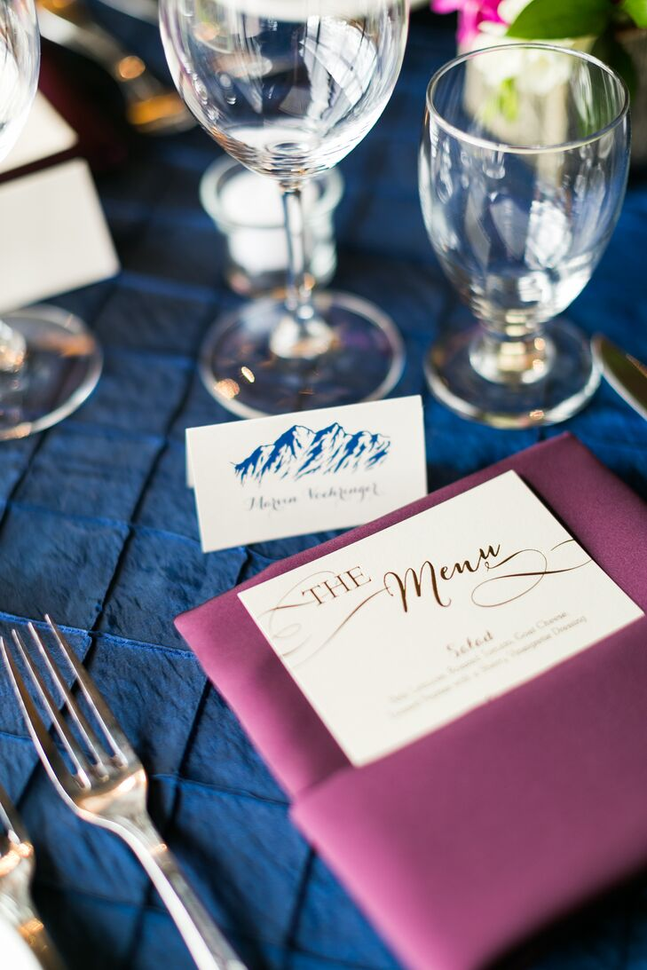 Each reception table was outfitted with textured navy pin-tuck tablecloths, which were accented by deep purple linens and mountain-stamped place cards.