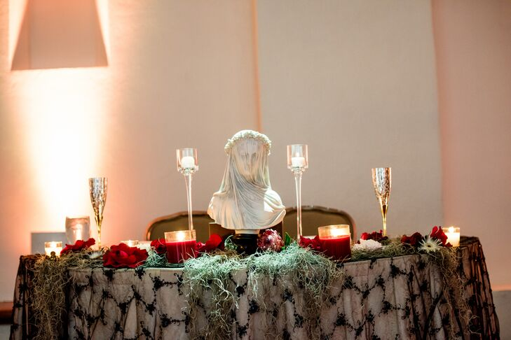 Candles, crimson accents and a porcelain bust decorated Lindsay and Justin's sweetheart table.